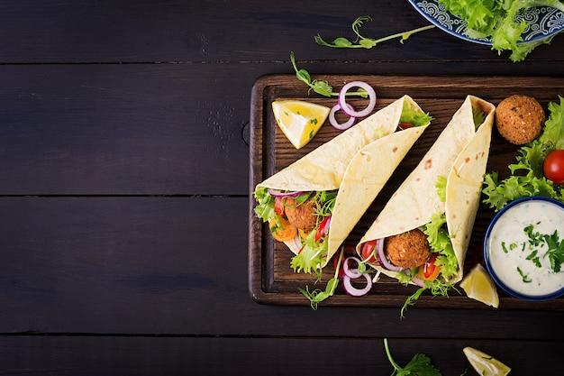 Tortilla envuelta con falafel y ensalada fresca. tacos veganos. comida vegetariana saludable. vista superior Foto gratis