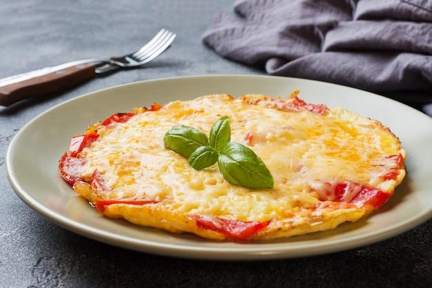 Tortilla, huevos revueltos con tomate y queso en un plato sobre una mesa oscura. Foto Premium