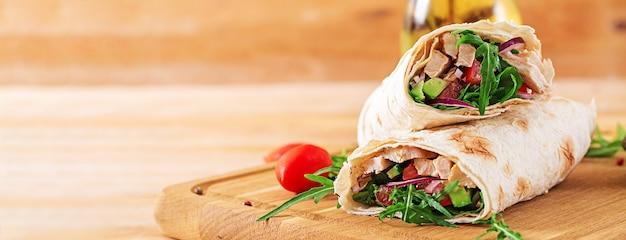 Las tortillas envuelven con el pollo y las verduras en fondo de madera. Foto Premium