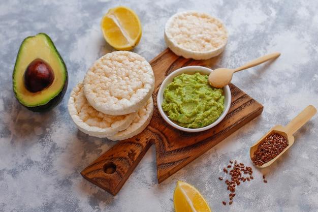 Tostada abierta de aguacate con pan de arroz, rodaja de limón, rodajas de aguacate, vista superior de semillas. Foto gratis