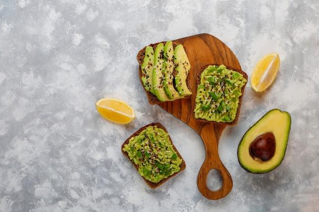 Tostada abierta de aguacate con rodajas de aguacate, limón, semillas de lino, semillas de sésamo, rebanadas de pan negro, vista superior Foto gratis