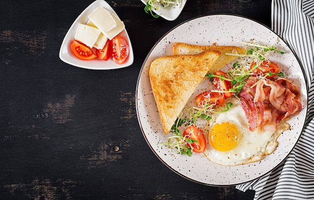 Tostadas, huevo, tocino y ensalada de tomates y microgreens. Foto gratis