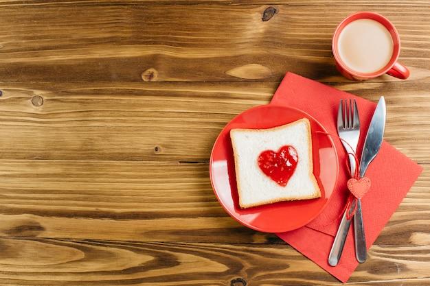 Tostadas con mermelada en forma de corazón con café. Foto gratis