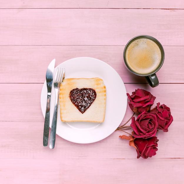 Tostadas con mermelada en forma de corazón con rosas y café. Foto gratis