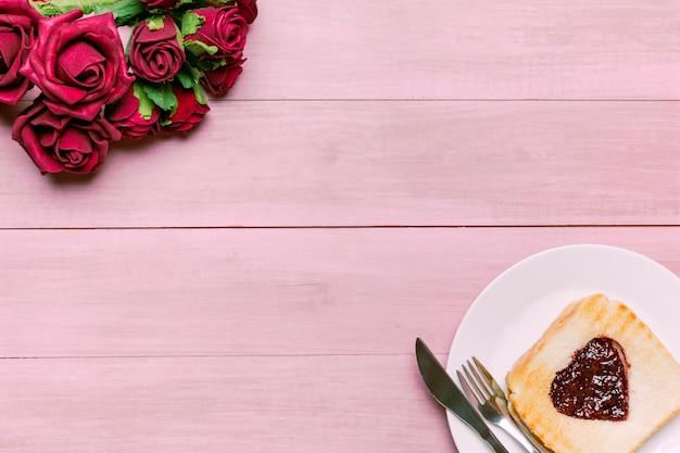 Tostadas con mermelada en forma de corazón con rosas rojas. Foto gratis