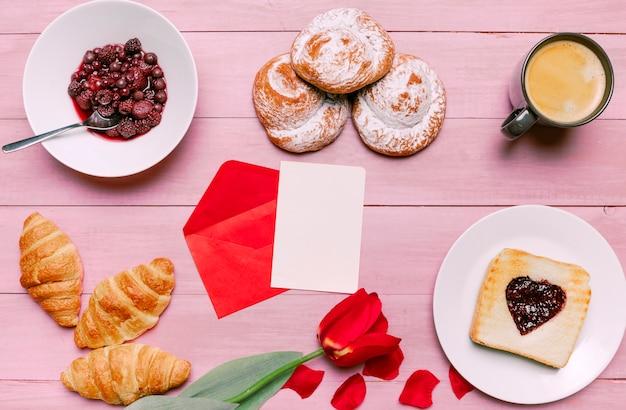 Tostadas con mermelada en forma de corazón con tulipanes, bayas y papel en blanco Foto gratis