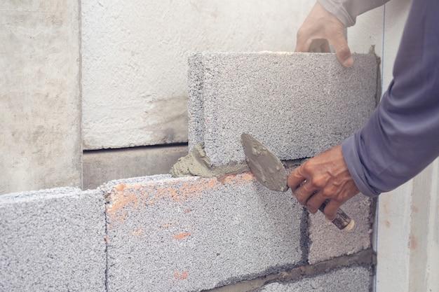 Trabajador de albañil instalando mampostería de ladrillo en la pared exterior con espátula Foto Premium