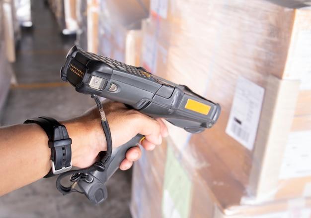 El trabajador del almacén está escaneando el escáner de código de barras con el envío. Foto Premium