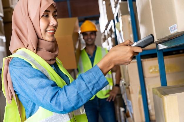 Trabajador de almacén femenino musulmán islam asiático haciendo inventario con escáner de código de barras Foto Premium