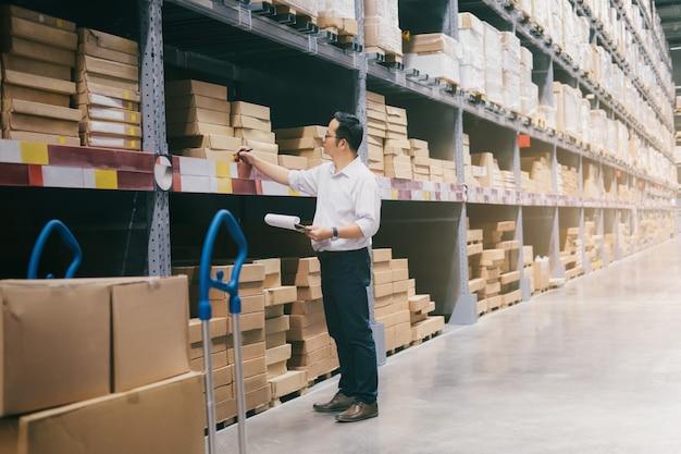 Trabajador del almacén del hombre que comprueba mercancías en el almacén. Foto Premium