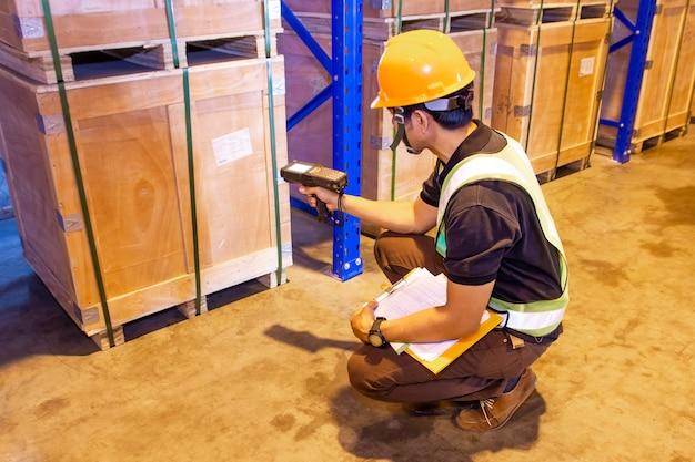 Trabajador del almacén que escanea el escáner de código de barras en una paleta de cajas pesadas en el almacén de almacenamiento Foto Premium