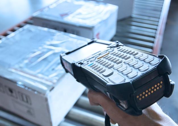 El trabajador de almacén tiene un escáner de código de barras con escaneo en cajas de paquetes Foto Premium