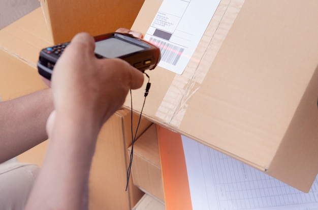 El trabajador del almacén tiene un escáner de códigos de barras con escaneo en la etiqueta de una caja de paquetes para enviar al cliente. Foto Premium