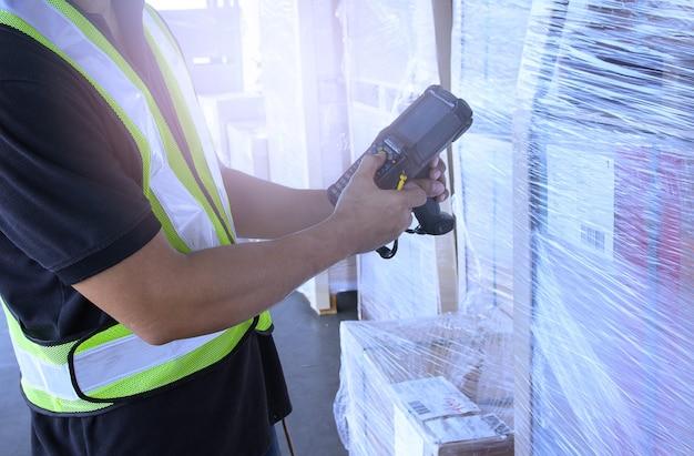 El trabajador del almacén tiene un escáner de códigos de barras con inventario y verifica los productos Foto Premium