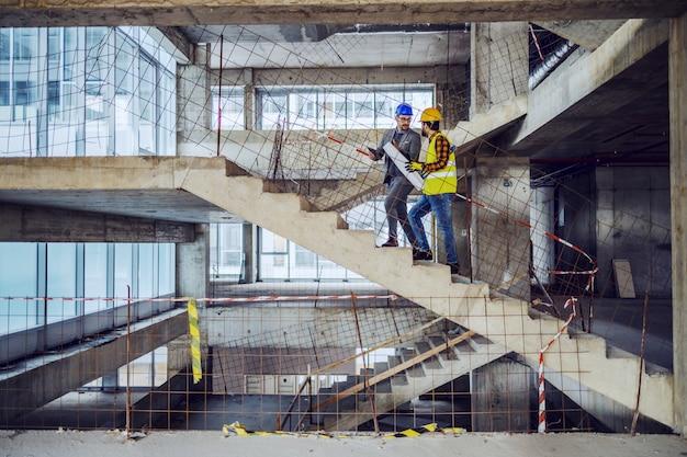 Trabajador de la construcción y arquitecto principal subiendo las escaleras y hablando sobre el progreso en la construcción del nuevo edificio. Foto Premium