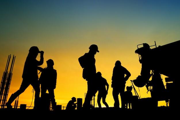 Trabajador de la construcción de la silueta hormigón que vierte durante los hormigones comerciales del edificio en sitio de construcción Foto Premium