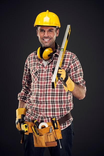 Trabajador de la construcción sonriente sosteniendo la medición Foto gratis