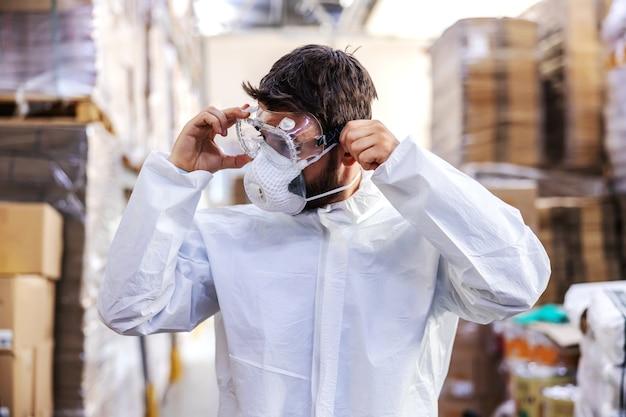 Trabajador dedicado en uniforme blanco estéril de pie en el almacén y poniéndose gafas protectoras y preparándose para esterilizar. concepto de brote de corona. Foto Premium