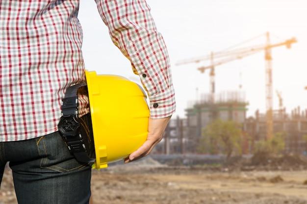 Trabajador del ingeniero de la mano que sostiene el casco de seguridad amarillo con la construcción en fondo del sitio.