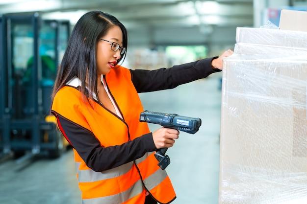 Trabajador escanea el paquete en el almacén de reenvío Foto Premium