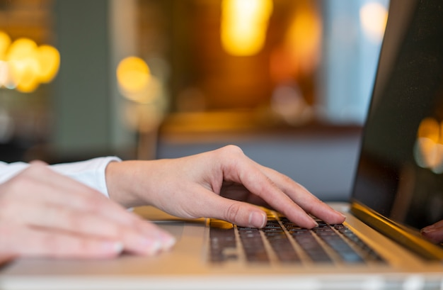 Trabajador escribiendo en la computadora portátil con bokeh Foto gratis