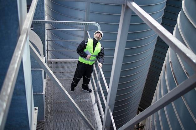 Trabajador de fábrica de pie sobre una plataforma metálica entre tanques de almacenamiento industrial y mirando hacia arriba para la inspección visual de los silos de producción de alimentos Foto gratis