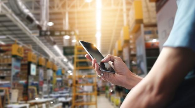 Trabajador de fábrica usando la aplicación en un teléfono inteligente móvil para operar la automatización para el comercio moderno. Foto Premium