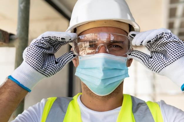 Trabajador con gafas de seguridad en un sitio en construcción Foto gratis