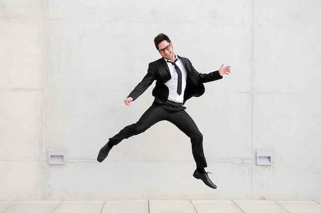 Trabajador con gafas y traje saltando Foto gratis