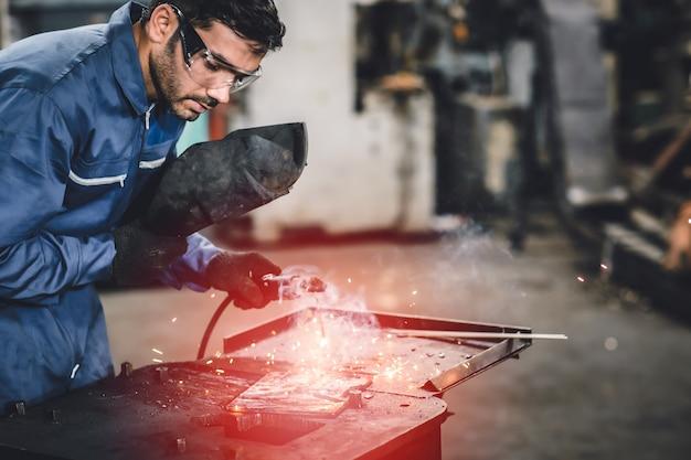 Trabajador de la industria de acero de soldadura tig con máscara de seguridad para proteger la vista en la fábrica de metal. Foto Premium