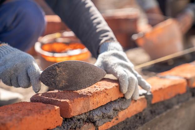 Trabajador industrial albañil instalando mampostería de ladrillo con espátula en el sitio de construcción Foto Premium
