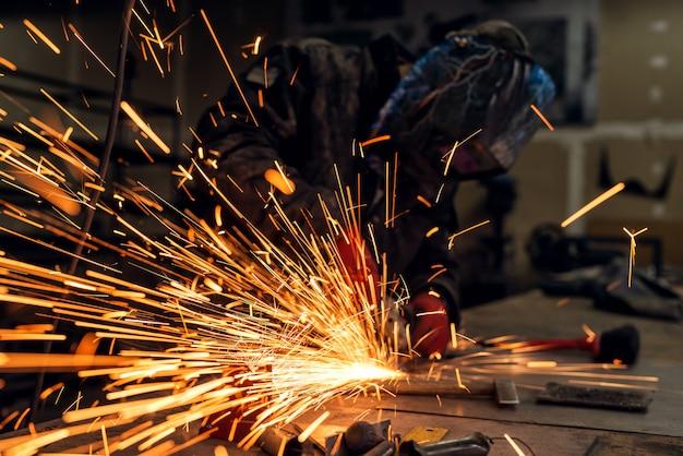 Trabajador industrial profesional con máscara de protección trabajando con amoladora eléctrica y muchas chispas en un taller de telas Foto Premium