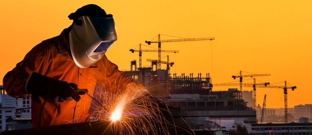 Trabajador industrial que suelda con autógena la estructura de acero para con el emplazamiento de la obra en fondo. Foto Premium