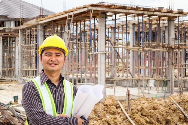 Trabajador de ingeniero de construcción de hombre de negocios asiático en casco protector y papel de planos en mano en el sitio de construcción de viviendas Foto Premium
