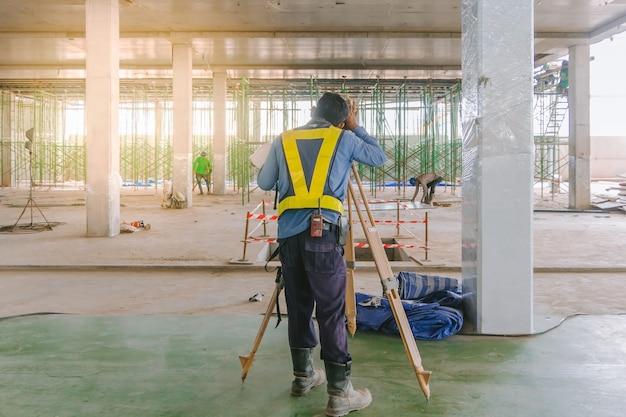 Trabajador del ingeniero del topógrafo que hace la medición con el equipo del teodolito en el emplazamiento de la obra. Foto Premium