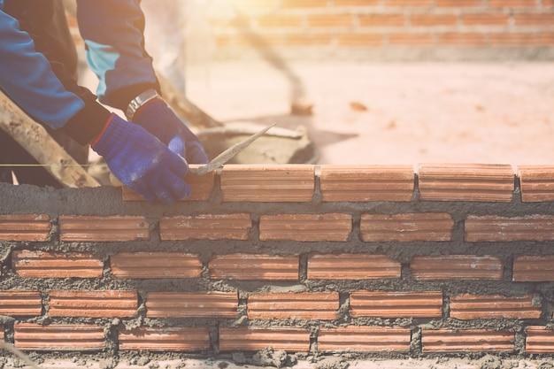 Trabajador instalando paredes de ladrillos en proceso de construcción de viviendas Foto Premium