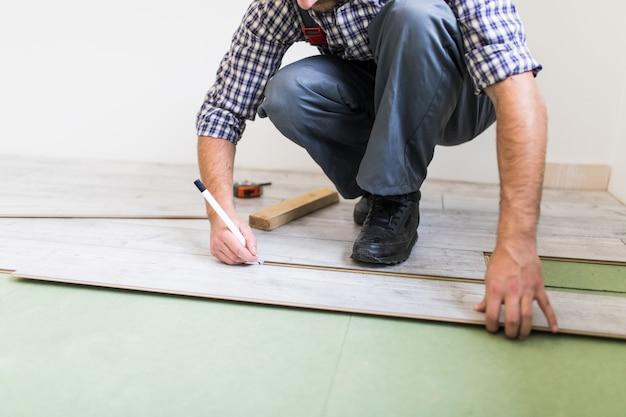 Trabajador joven que recubre un piso con tablas de piso laminado Foto gratis