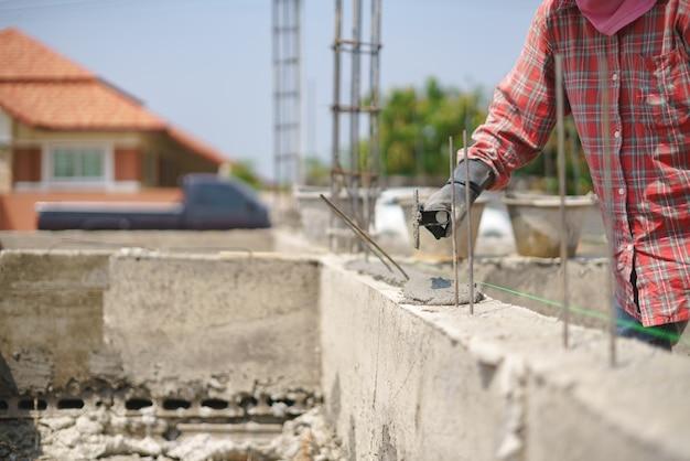 Trabajador de mano de obra construyendo muro con cemento de concreto Foto Premium