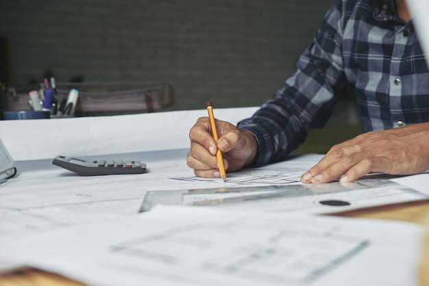 Trabajador de la oficina de arquitectura dibujando bocetos en la oficina Foto gratis