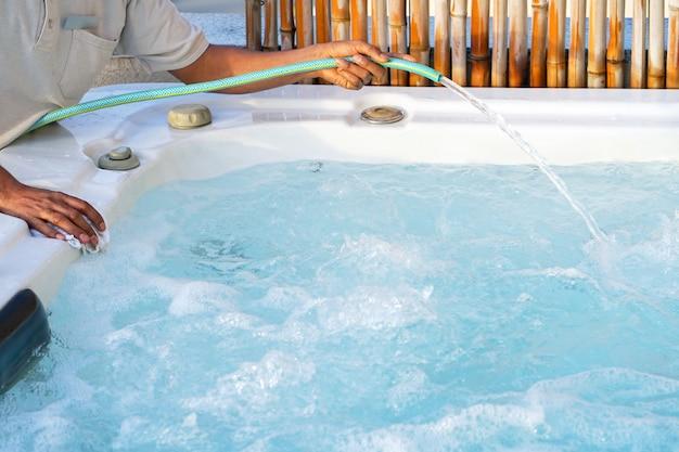 Trabajador del personal del hotel africano limpiando la piscina Foto Premium