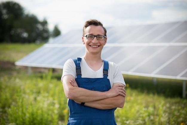 Trabajador de pie en el campo con energía solar con paneles solares en el backstage. Foto Premium