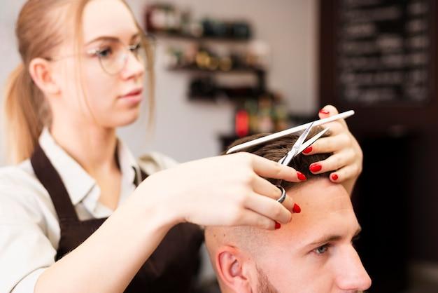 Trabajador profesional de peluquería haciendo su trabajo Foto gratis