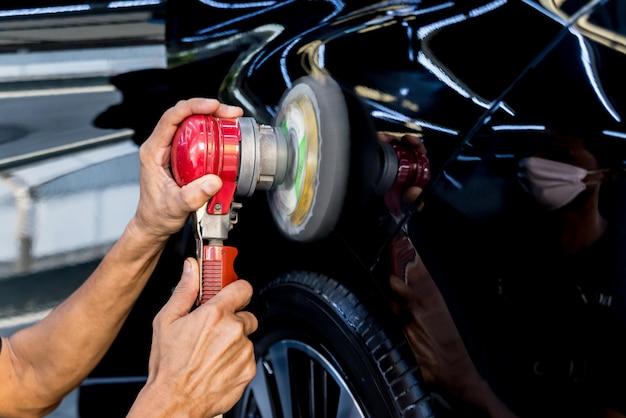El trabajador pule un automóvil con la herramienta eléctrica. Foto Premium