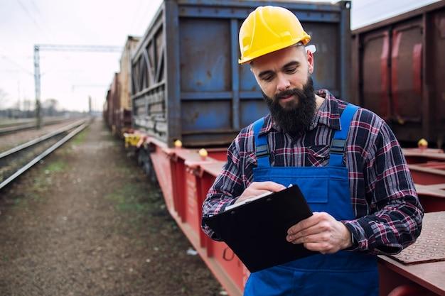 Trabajador que envía contenedores de carga para compañías navieras a través de un tren de carga y organiza las mercancías para su exportación. Foto gratis