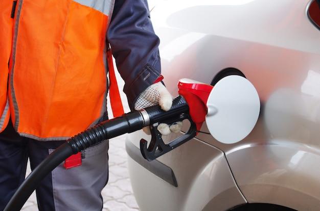 El trabajador de reabastecimiento reabastece el automóvil con gasolina Foto Premium
