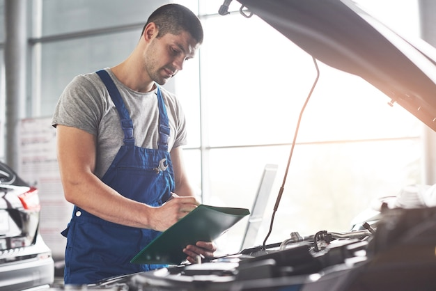 Trabajador de servicio de coche musculoso reparando vehículo. Foto gratis