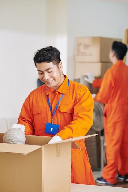 Trabajador de servicio en movimiento empacando objetos frágiles Foto Premium