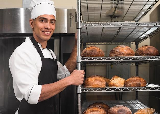 Trabajador de sexo masculino hermoso en uniforme que lleva estantes con la barra de pan en la panadería Foto gratis