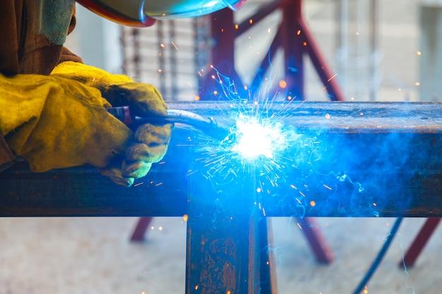 Trabajador de soldadura en una fábrica. soldadura en una planta industrial. Foto Premium