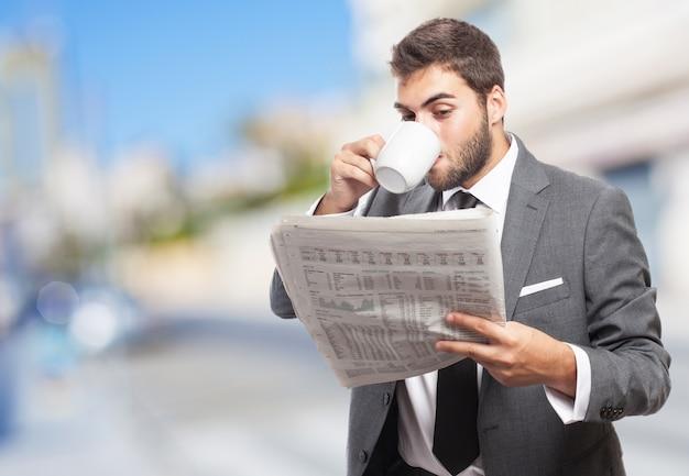 Trabajador con taza de café leyendo las noticias Foto gratis